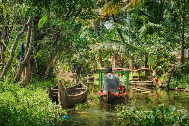 Alleppey, india - 29 januari 2016: kleine toeristische boot op prachtige binnenwateren landschap met palmbomen op de achtergrond, kerala, india