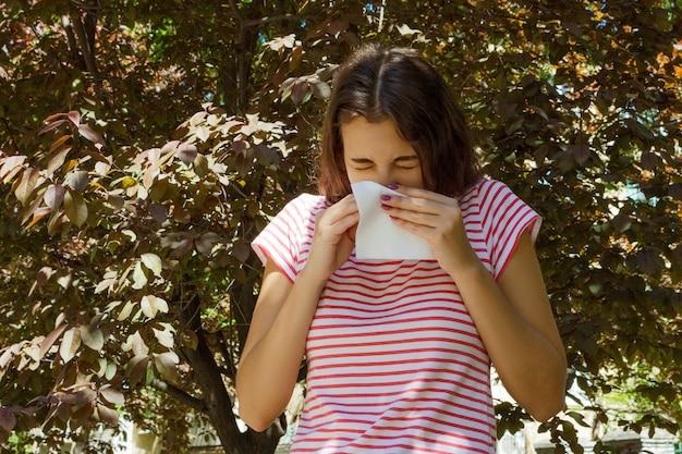 Allergie concept. niezend jong meisje met neuswisser onder bloeiende bomen in park