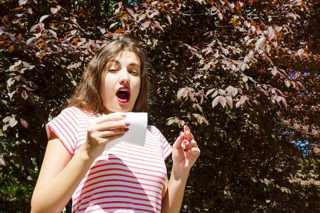 Allergie-concept. niezend jong meisje met neuswisser onder bloeiende bomen in park