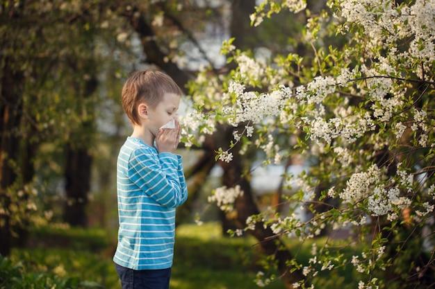 Allergie concept. weinig jongen blaast zijn neus dichtbij tot bloei komende bloemen