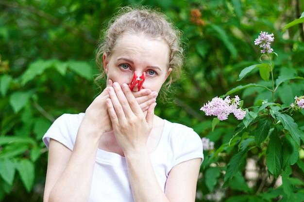 Allergie. vrouw kneep met de hand in haar neus om niet te niezen van het stuifmeel van bloemen.