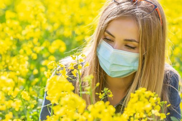 Allergisch blond meisje met een beschermend masker kijkt naar de gele bloem zittend op een weide.