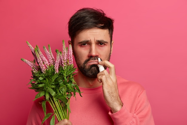 Allergische bebaarde man houdt plant vast, gebruikt neusdruppels om niezen te genezen, heeft een ontevreden gezichtsuitdrukking, reactie op allergeen, geneest de zeeënziekte, volgt het advies van een allergoloog op. gezondheidszorg concept