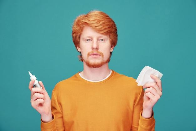 Allergische jongeman met rode baard met verstopte neuzen en neusspray en servet gebruikt, blauw