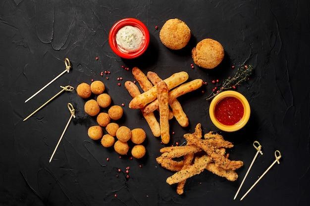Allerlei gefrituurde snacks met twee verschillende sauzen op zwarte achtergrond close-up bovenaanzicht