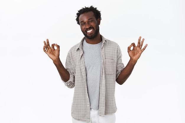 Alles gaaf. chill en ontspannen, zorgeloze onbezorgde afro-amerikaanse bebaarde man in casual outfit