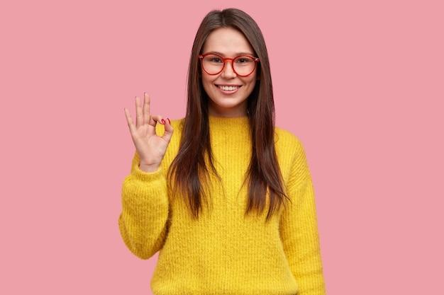 Alles is in orde en onder controle. gelukkig positieve vrouw toont oke gebaar, demonstreert goedkeuring van idee