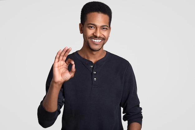 Alles is in orde of geweldig! positieve lachende hipster man met donkere gezonde huid, toont goed gebaar, keurt goed idee van vriend goed, staat tegen witte muur. lichaamstaal concept