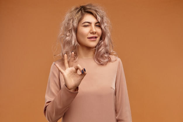 Alles onder controle. geïsoleerde schot van schattige zelfverzekerde jonge europese vrouw met stijlvol kapsel en neusring duim en wijsvinger verbinden