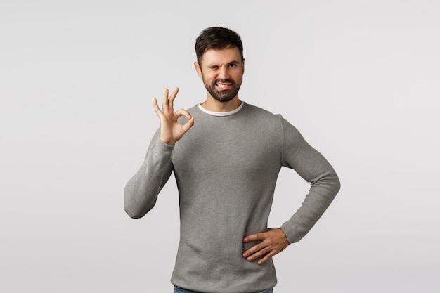Alles onder controle. sassy, assertieve charismatische bebaarde man in grijze trui, knipoog zelfverzekerd, kan niet op mij vertrouwen, toon oke, ok gebaar, keur product goed, zoals idee, accepteer plan