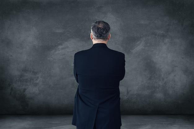 Alles over vertrouwen. achteraanzicht van volwassen zakenman die zijn armen gekruist houdt terwijl hij tegen een grijze achtergrond staat met kopieerruimte