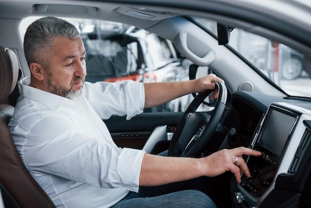 Alles werkt perfect. senior zakenman in officiële kleding zit in een luxeauto en het indrukken van de knoppen op de muziekspeler