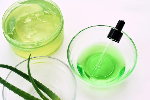 Aloë gel, aloë vera bladeren en groen serum van natuurlijke ingrediënten op een witte achtergrond. thuis cosmetica maken