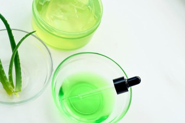 Aloë-gel, bladeren van planten en groen serum van natuurlijke extracten op een witte achtergrond. hydrateert de huid met aloë-gel
