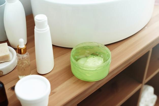 Aloë-gel in een plastic pot naast vochtinbrengende producten