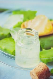 Aloë vera extract in een klein flesje en stukjes op tafel. selectieve aandacht.