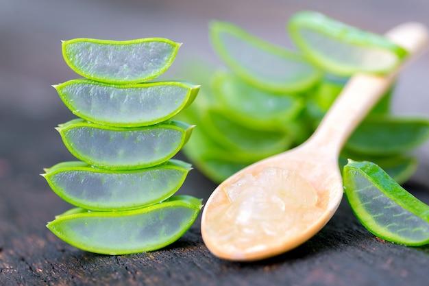 Aloë vera op houten lepel op houten tafel er zijn veel nuttige kruiden.