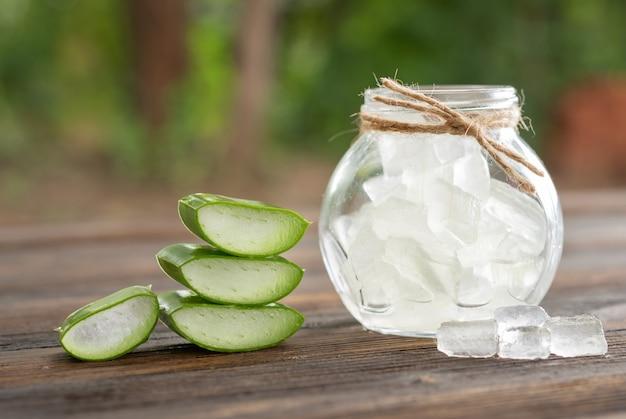 Aloë vera op product display houten teller achtergrond. aloë vera is een tropische groene plant. gesneden aloë vera natuurlijke organische vernieuwingscosmetica, alternatieve geneeskunde. biologisch huidverzorgingsconcept.