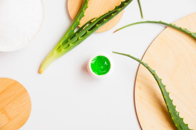 Aloë vera vertrekt met een cosmetische crèmekleurige fles