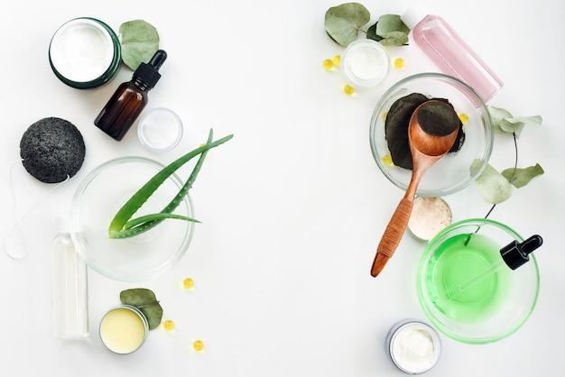Aloë verabladeren, zwarte kleipoeder, eucalyptusbladeren, vitamine c, bloemextract, flessen met serums, tonics, potjes crème en gel op een witte achtergrond. het concept van huidverzorging, de hydratatie ervan