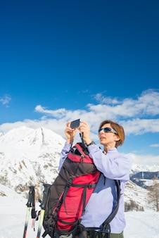 Alpinist die foto met telefoon neemt