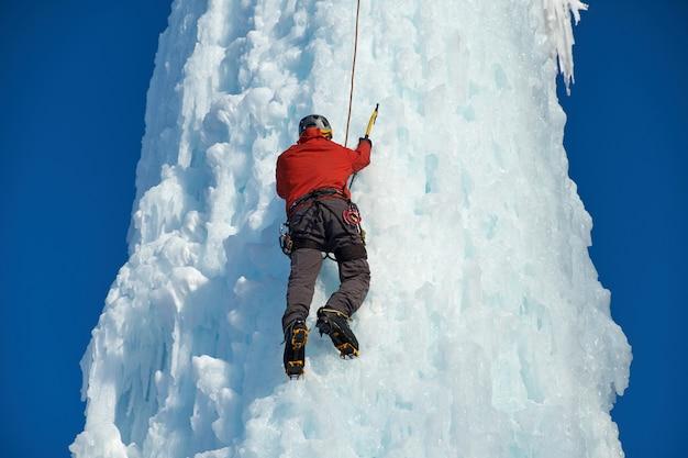 Alpinistische man met ijsgereedschap bijl beklimmen van een grote muur van ijs. buitensport portret.