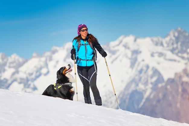 Alpinistische vrouw op ski's en zeehondenhuiden alleen met zijn hond trouwe vriend