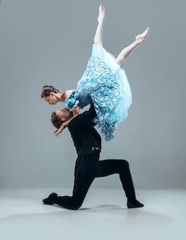 Als een wolk. mooie eigentijdse balzaaldansers die op grijze muur worden geïsoleerd. sensuele professionele artiesten die walz, tango, slowfox en quickstep dansen. flexibel en gewichtloos.