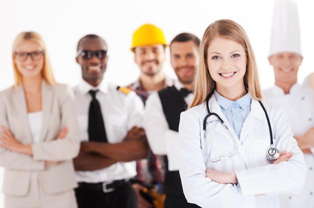 Als ik groot ben, word ik dokter. mooie jonge vrouwelijke arts die armen gekruist houdt en glimlacht terwijl een groep mensen in verschillende beroepen op de achtergrond staat