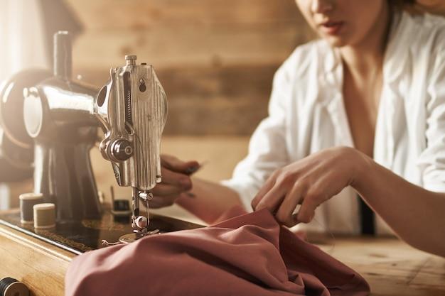 Als je geen kleding kunt kopen, naai er dan een. bijgesneden schot van vrouwelijke kledingstuk maken op naaimachine, het creëren van nieuwe jurk in de werkplaats, wordt geconcentreerd en geconcentreerd. nieuwe naaister die op tijd klaar is met werken