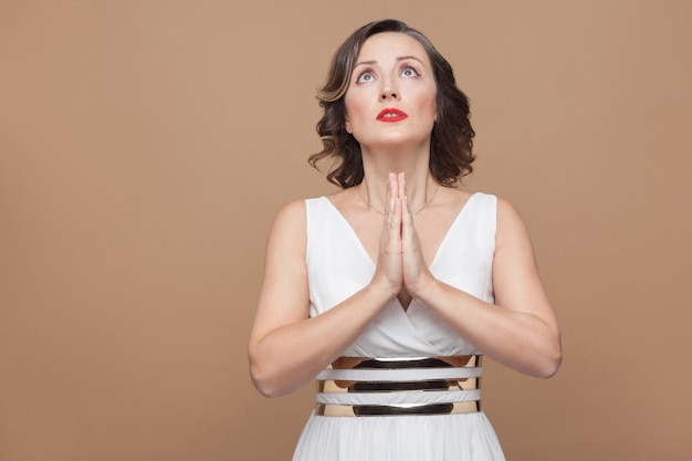 Alsjeblieft god! vrouw bidt en kijkt omhoog. emotioneel uitdrukkende vrouw in witte jurk, rode lippen en donker krullend kapsel. studio-opname, binnen, geïsoleerd op beige of lichtbruine achtergrond