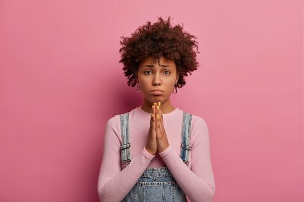 Alsjeblieft, ik smeek je. treurige etnische vrouw met donkere huid houdt handen vast in gebed, vraagt om verontschuldiging of hulp, portemonneert onderlip, heeft krullend kapsel, draagt losse coltrui, smeekt vriend om haar te vergeven