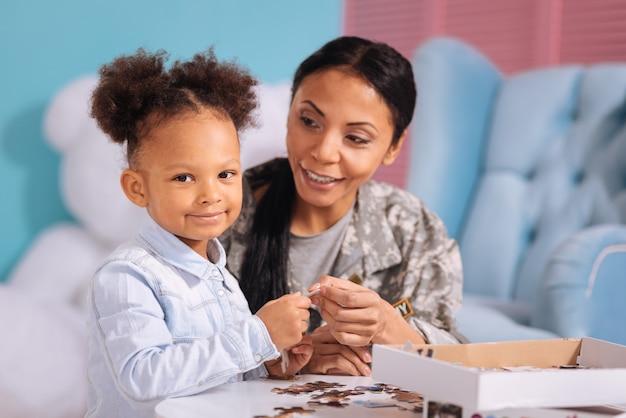 Alsjeblieft. ondersteunende, zorgzame geweldige moeder die haar kind een ontbrekend stuk geeft en een foto voltooit terwijl ze hun vrije tijd thuis doorbrengen