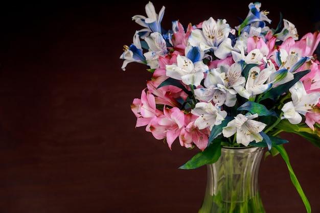 Alstroemeria bloemen in glazen vaas op donkere ondergrond. moederdag.
