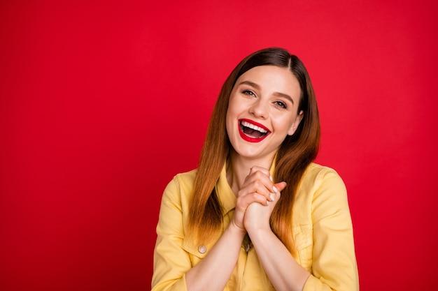 Alstublieft. foto van aantrekkelijke dolblije dame goed humeur houd de armen bij elkaar tevreden onverwacht leuk cadeau vakantie slijtage casual gele blazer jas geïsoleerd levendige rode kleur achtergrond
