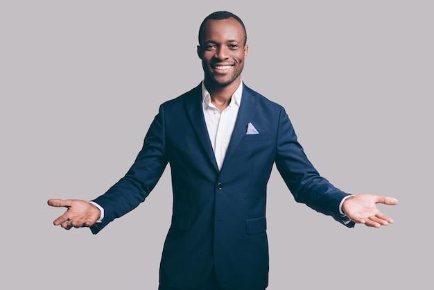 Alstublieft! knappe jonge afrikaanse man in slim casual jasje gebaren en glimlachen terwijl hij staat