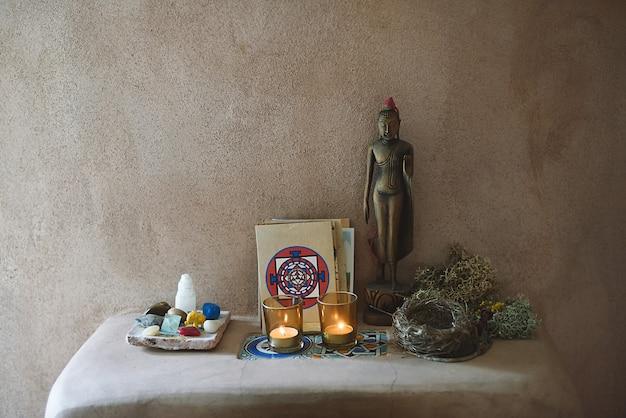 Altaar in adobe interieur met boeddha, kristallen, kaarsen, mandala's.