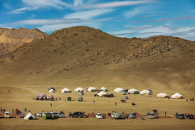 Altai-bergen en vallei met kleine mongoolse yurts en auto's in west-mongolië