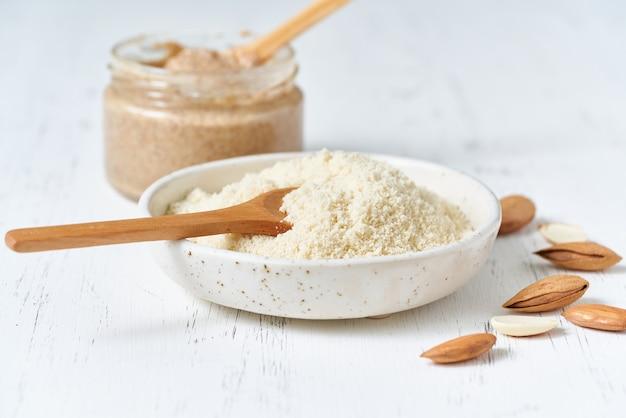 Alternatief amandelmeel. geraspte gemalen amandelen, gehakt in een blender, bord, lepel, noten