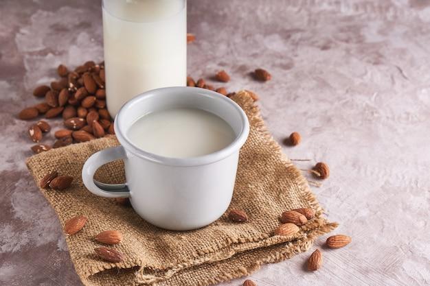 Alternatief eten en drinken. eigengemaakte amandelmelk in een kop en een fles, amandelpitten op de rustieke ruimte van het oppervlakteexemplaar