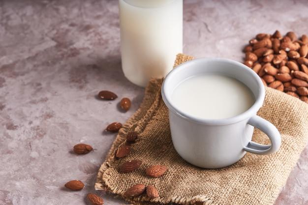 Alternatief eten en drinken. eigengemaakte amandelmelk in een kop en een fles, amandelpitten op rustieke oppervlakte.