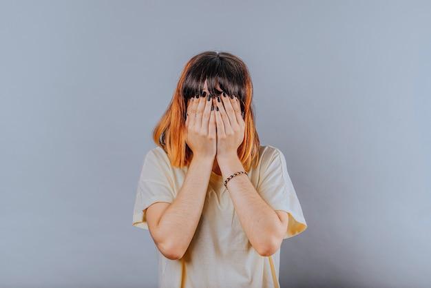 Alternatief model met oranje haren in portret over haar gezicht met beide handen.