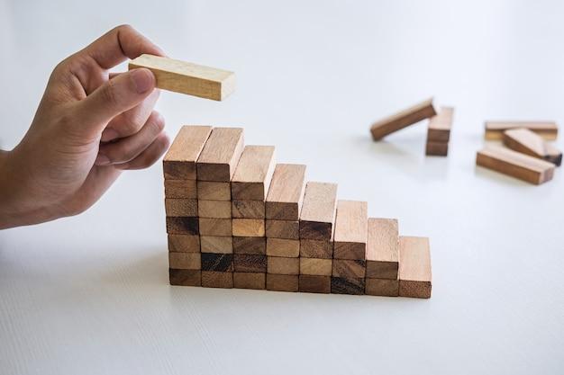 Alternatief risico en strategie in het bedrijfsleven om groei te maken, beeld van de hand van de zakenman die een houten blokhiërarchie stapelt om te groeien om de basis en ontwikkeling succesvol te maken