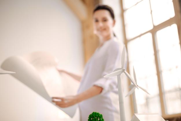 Alternatieve energie. selectieve focus van windmolenmodellen met brunette zwangere vrouw die verblijft en blauwdruk bestudeert