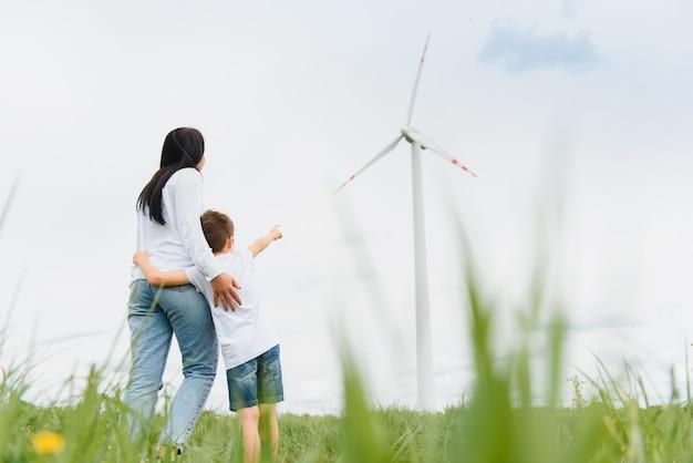 Alternatieve energie, windmolenpark en fijne tijd met je gezin. gelukkige moeder op de weg met zijn zoon op vakantie en ontsnappen naar de natuur.