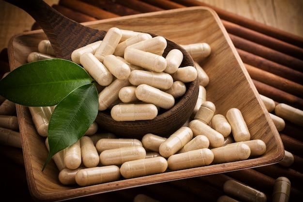 Alternatieve geneeskundetabletten op een houten lepel, groen blad.