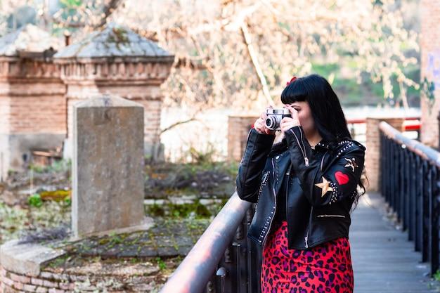 Alternatieve getatoeëerde vrouw met leren jas en een bloem in haar haar die een foto maakt op een brug met een vintage camera.
