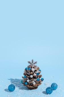 Alternatieve kerstboom gemaakt van dennenappels met kralen en sneeuw op een blauwe achtergrond met een harde schaduw