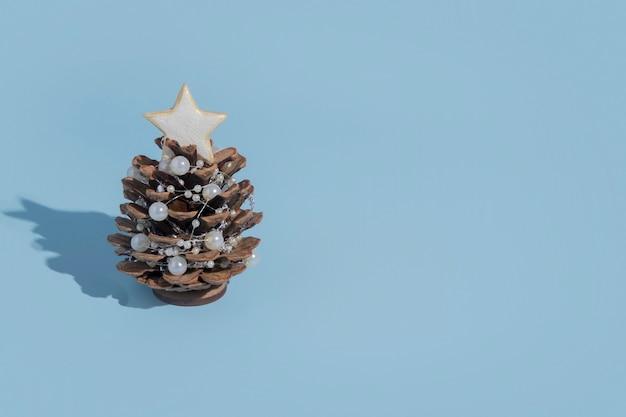 Alternatieve kerstboom gemaakt van dennenappels met kralen op een blauwe achtergrond met een harde schaduw met kopie ruimte in een minimalistische stijl voor een nieuwjaarskaart