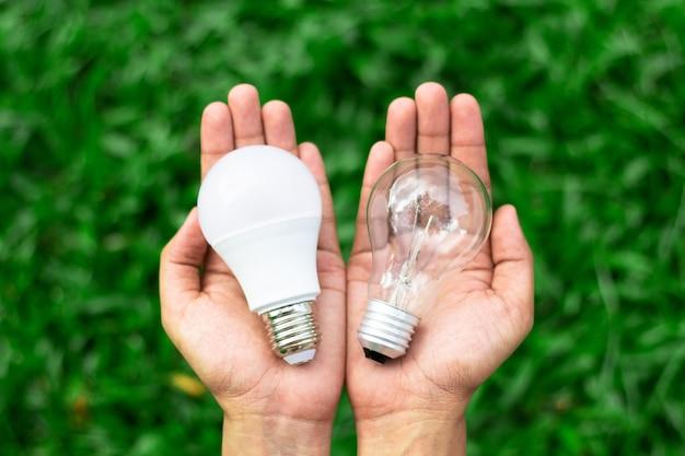 Alternatieve technologie concept. handen die leidene bol en fluorescente bol houden die binnen vergelijken
